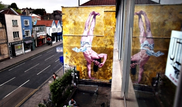 Controversial Mural Of Breakdancing Jesus Is Unveiled...BRISTOL, ENGLAND - JUNE 11:  General view ofCosmo Sarson's mural of Jesus breakdancing that he has painted on the 8.5 metre wall beside The Canteen in Stokes Croft and is being officially unveiled this evening is reflected in a window, on June 11, 2012 in Bristol, England. The artist was commissioned by The Canteen to paint the wall, which is directly opposite Banksy's Mild Mild West. The controversial 'Breakdancing Jesus', which took 4 days to paint and involved a kilo of glitter and was inspired by an actual event in the Vatican where breakdancers performed to an applauding Pope John Paul II in 2004, is likely to be the latest attraction for graffiti tourists visiting Bristol, often seen the spiritual home of underground artist Banksy. (Photo by Matt Cardy/Getty Images)